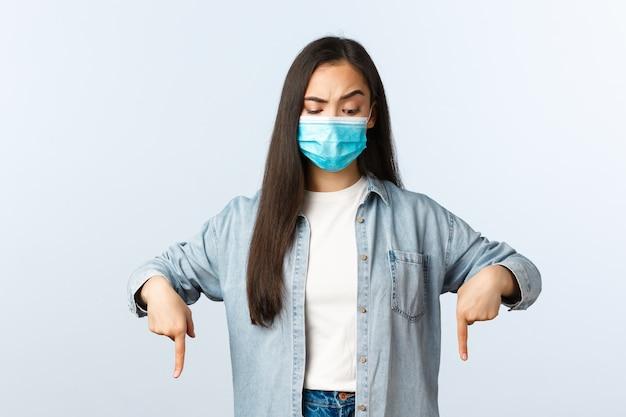 Sceptisch en verward aziatische vrouw in medische masker, casual kleding, naar beneden te kijken