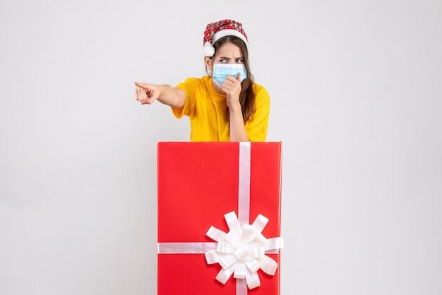 Sceptisch meisje met kerstmuts wijzend op iets achter grote kerstcadeau op wit