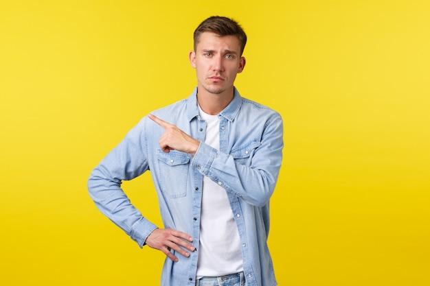 Sceptische arrogante blonde knappe kerel die fronst en ongehinderd kijkt terwijl hij de linkerbovenhoek wijst naar een onamusante gemiddelde promobanner, staande op een gele achtergrond.