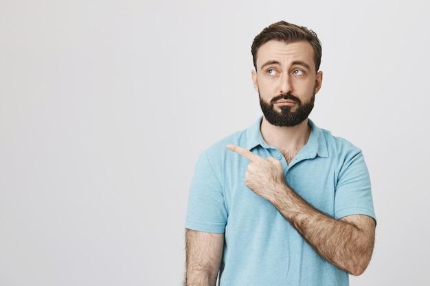 Sceptische bebaarde man kijkt en wijst links niet onder de indruk