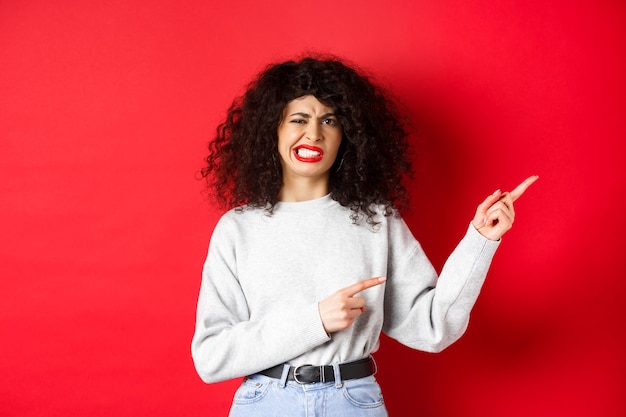 Sceptische blanke vrouw ontevreden grimassen, klagen over slechte smaak, vingers naar rechts wijzend en ineenkrimpen van afkeer, staande tegen een rode achtergrond.