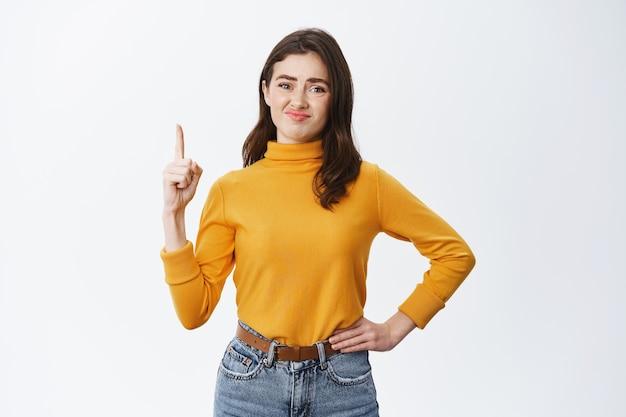 Sceptische brunette vrouw grijnst en kijkt twijfelachtig, wijzende vinger omhoog op de bovenste advertentie, slechte gemiddelde promotie tonend, staande tegen een witte muur