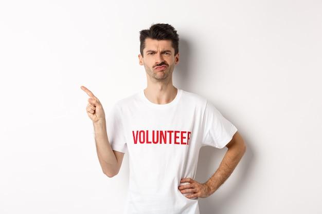 Sceptische en aarzelende mannelijke vrijwilliger in t-shirt grimassen twijfelachtig, wijzende vinger links naar promo-aanbieding, witte achtergrond