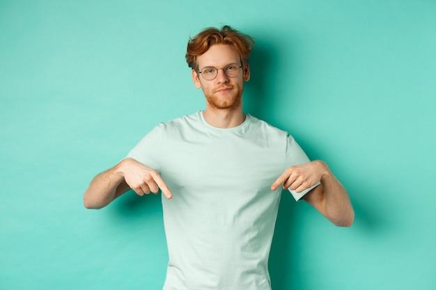 Sceptische en gehinderde man met rood haar en baard, bril en t-shirt dragend, grijns en vinger naar beneden wijzend, promo tonend met oordeelkundig gezicht, turkooizen achtergrond