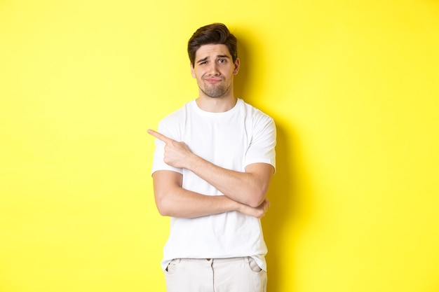 Sceptische en onwillige man in wit t-shirt, vinger naar links wijzend en ongeamuseerd grijnzend, slechte reclame tonend, staande over gele achtergrond