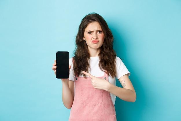 Sceptische en overstuur jonge vrouw fronsend, mokkend teleurgesteld terwijl ze naar een leeg smartphonescherm wijst met een slecht online aanbod of app, staande tegen een blauwe achtergrond.