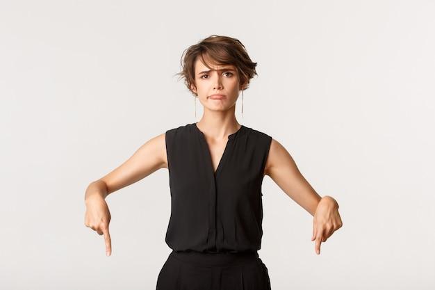 Sceptische en teleurgestelde jonge vrouw die klaagt, ontevreden grijnst en met de vingers naar beneden wijst.