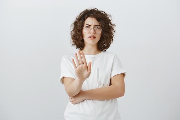 Sceptische en teleurgestelde vrouw die stopgebaar toont en ineenkrimpt van afkeer, weigert, aanbod afwijst