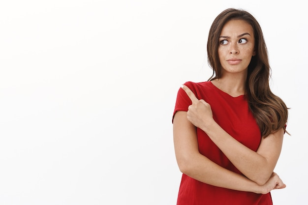 Sceptische en twijfelachtige jonge bezorgde vrouw die aarzelt over iets vreemds dat wijst en naar de linkerbovenhoek staart met een ontevreden grijns, niet onder de indruk
