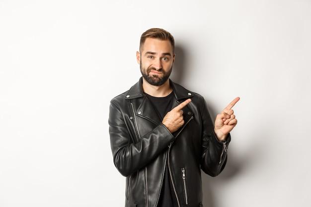 Sceptische en twijfelachtige man in zwart leren jack, schouderophalend terwijl hij naar de promo-aanbieding rechtsboven wijst, staand