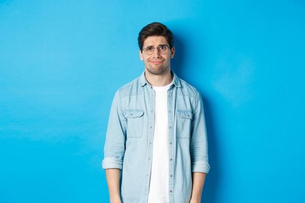 Sceptische en twijfelachtige man met een bril, verward kijkend naar iets vreemds, blauwe achtergrond