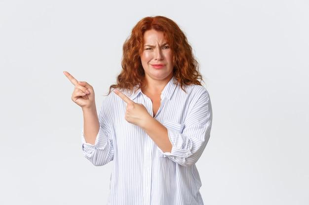 Sceptische en veroordelende roodharige vrouw van middelbare leeftijd wijzend linksboven