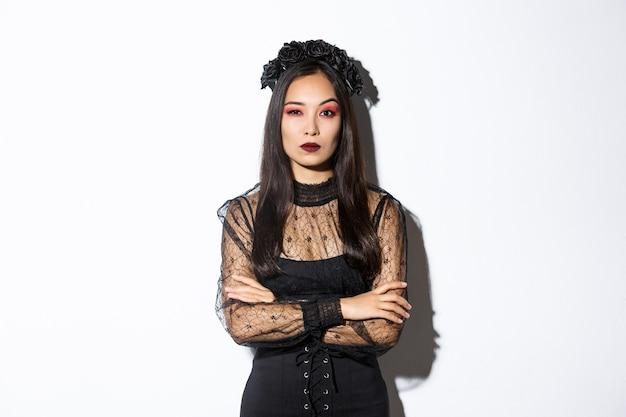 Sceptische jonge aziatische vrouw die in heks of weduwenkostuum twijfelachtig kijkt.