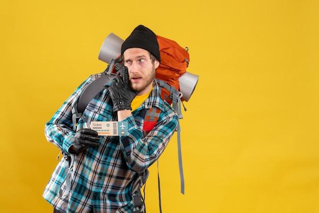 Sceptische jonge backpacker met zwarte hoed met vliegticket