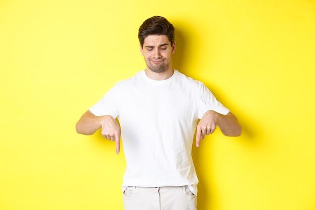 Sceptische jonge man in wit t-shirt, wijzend en neerkijkt van streek, keurt het product af en houdt niet van, staande over gele achtergrond.