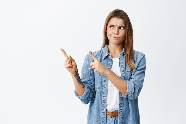 Sceptische jonge vrouw die twijfelt, grijns en ontevreden fronst naar het logo, wijzend en kijkend naar de linkerbovenhoek, staande tegen de witte muur