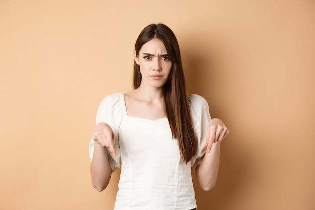 Sceptische jonge vrouw fronst, handen naar beneden wijzend op iets slechts of teleurstellend, kijkt boos, staande op beige achtergrond.