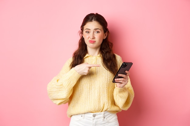 Sceptische jonge vrouw grijnzende ontevreden wijzende vinger naar het smartphonescherm met twijfels over online inhoud die tegen de roze muur staat