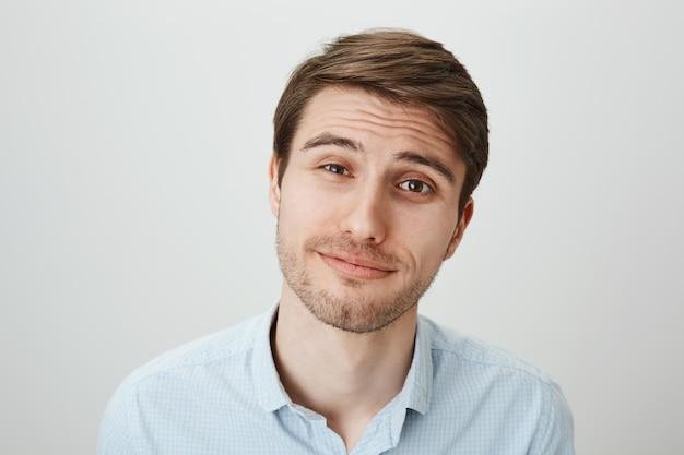 Sceptische jongeman glimlachend en wenkbrauwen verhogen ongeloof