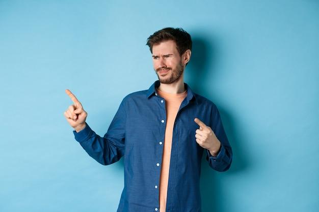 Sceptische jongeman wijst en kijkt naar links met teleurstelling, ineenkrimpen van iets slechts, staande boos op blauwe achtergrond.