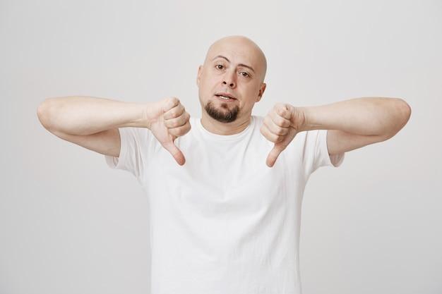 Sceptische kale, bebaarde man toont zijn duimen en is teleurgesteld
