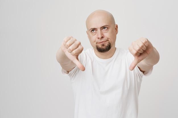 Sceptische kale, bebaarde man toont zijn duimen naar beneden en rolt zijn ogen