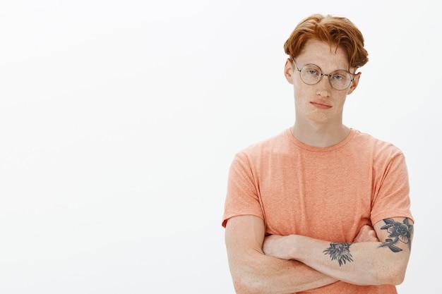 Sceptische knappe roodharige man met bril, kruis armen op de borst en op zoek naar onaangenaam