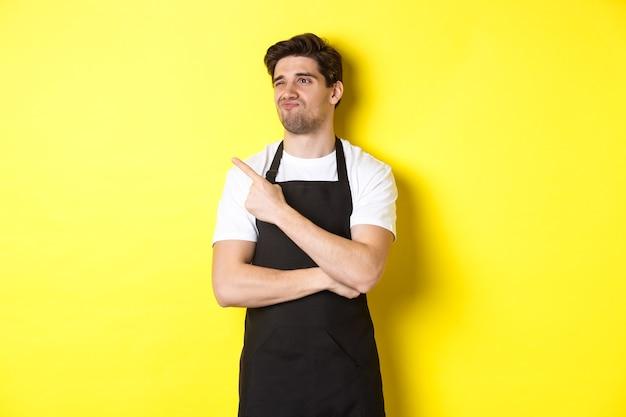 Sceptische mannelijke verkoper in zwarte schort die ontevreden kijkt, grimassend en links naar advertentie wijst, staande over gele achtergrond.