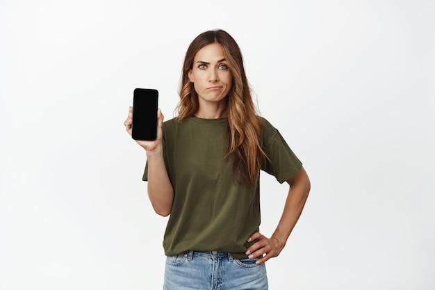 Sceptische, overstuur vrouw van middelbare leeftijd, moeder die het scherm van de mobiele telefoon laat zien met een ontevreden grijnsgezicht