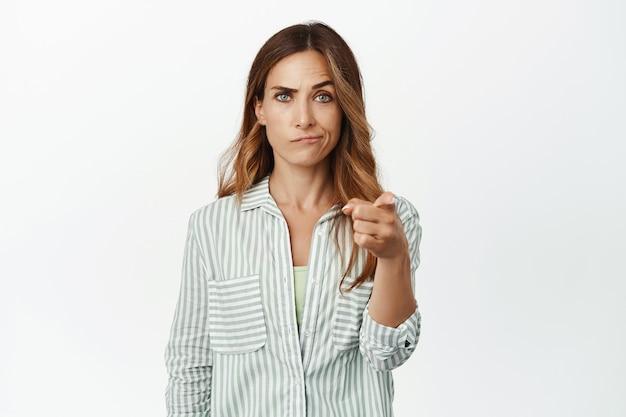 Sceptische, veroordelende vrouw grijns, wenkbrauw optrekken verdacht, wijzende vinger naar voren twijfelachtig
