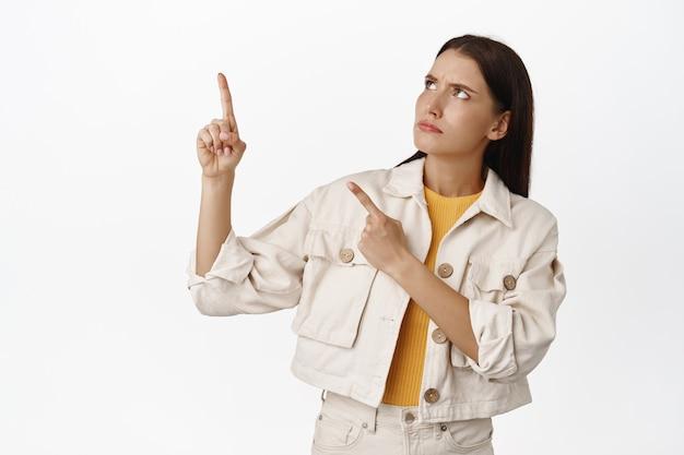 Sceptische vrouw fronst wenkbrauwen, wijst en kijkt naar de linkerbovenhoek met een serieus, twijfelachtig gezicht, denkend, onzeker voelend over iets op wit.