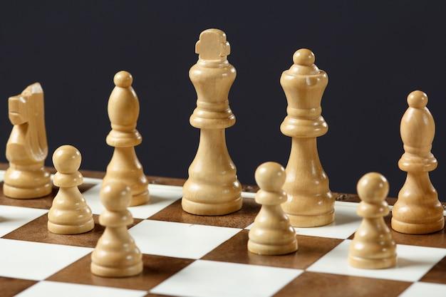 Schaakbord met schaakstukken op grijze achtergrond selectieve focus op witte koning.
