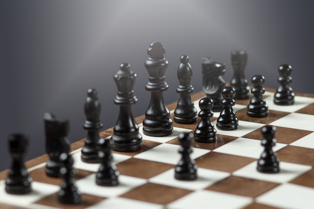 Schaakbord met zwarte schaakstukken op grijze achtergrond