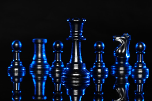 Schaakcijfers op zwarte achtergrond met blauwe achtergrondverlichting