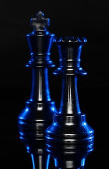 Schaakfiguren op zwart met blauwe achtergrondverlichting