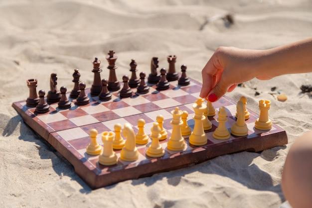 Schaakspel op het bord op het strand, schaakbord op het zand op een zonnige dag.