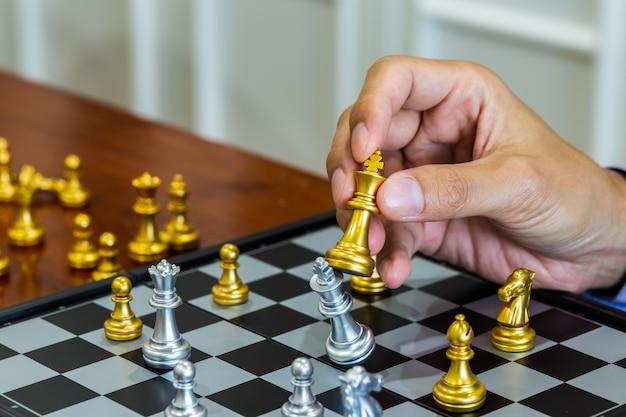 Schaakspel op schaakbord achter zakenman achtergrond. bedrijfsconcept om financiële informatie en marketingstrategieanalyse voor te stellen.