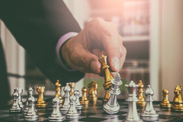 Schaakspel op schaakbord achter zakenmanachtergrond