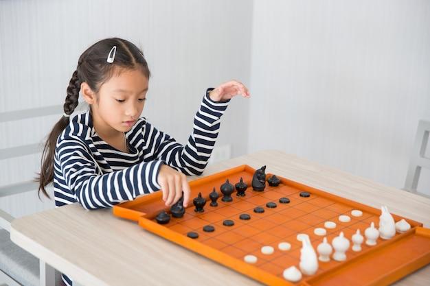 Schaakspel spelen door klein meisje in de woonkamer