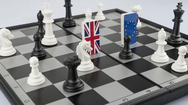 Schaakstukken en vlaggen van de europese unie en groot-brittannië op een schaakbord politiek spel