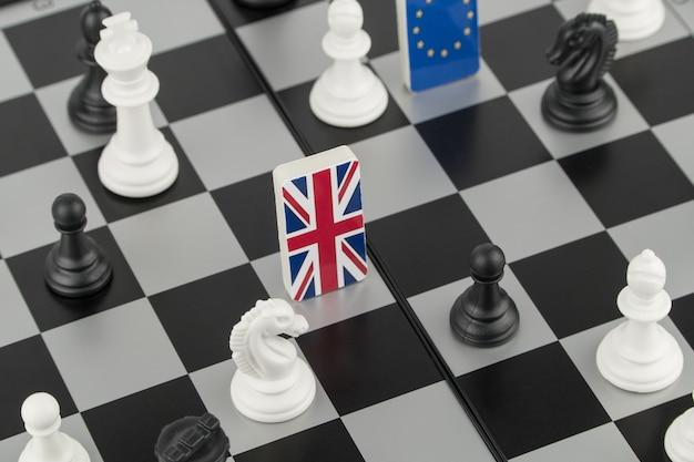 Schaakstukken en vlaggen van de europese unie en groot-brittannië op een schaakbord