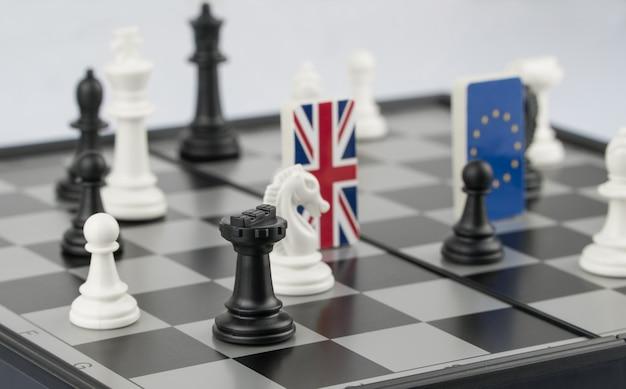 Schaakstukken en vlaggen van de europese unie en het vk op een schaakbord