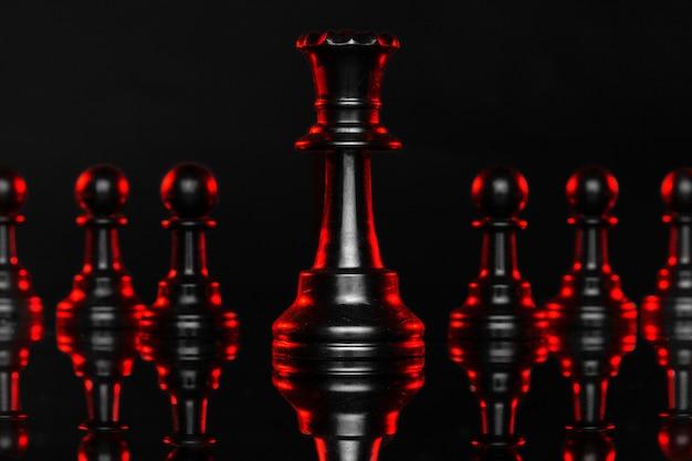 Schaakstukken op donker met rode achtergrondverlichting sluiten omhoog