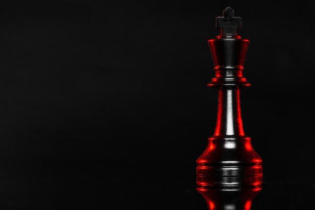 Schaakstukken op donkere achtergrond met rode achtergrondverlichting close-up