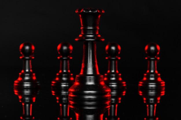 Schaakstukken op donkere achtergrond met rode achtergrondverlichting