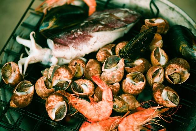 Schaaldieren gegrilde zeevruchten op fornuis. krab garnalen garnalen inktvis mosselen gekookt branden op grill barbecue feestje op het strand