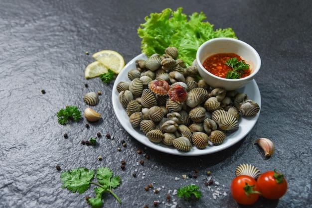 Schaaldieren zeevruchten plaat kokkels verse rauwe oceaan gourmetdiner met kruiden en specerijen