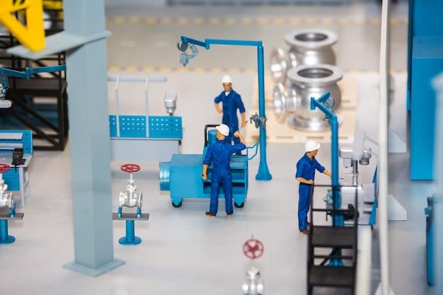 Schaalmodel van fabrieksinstallatie met arbeider die aan de machine werkt