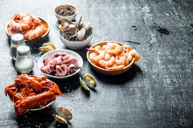 Schaaltjes voor babygarnalen, oesters, rivierkreeften en octopus. op donkere rustieke achtergrond