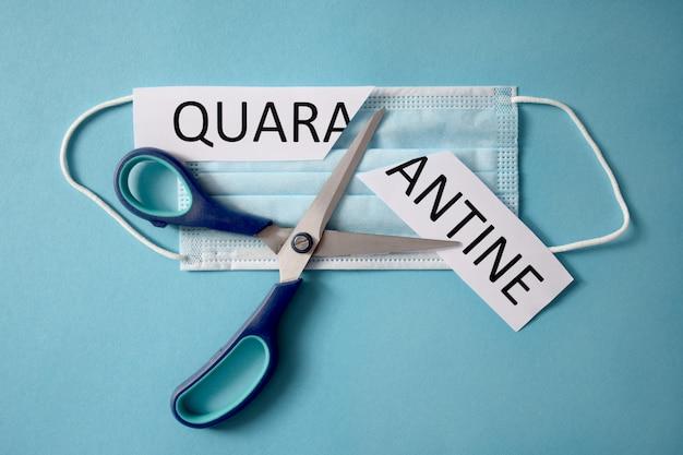 Schaar die een beschermend masker en stuk papier met quarantainewoord snijdt. isolatie is voorbij. terug naar het normale leven. ontspannende quarantainebeperkingen. na het afsluiten van het coronavirus.